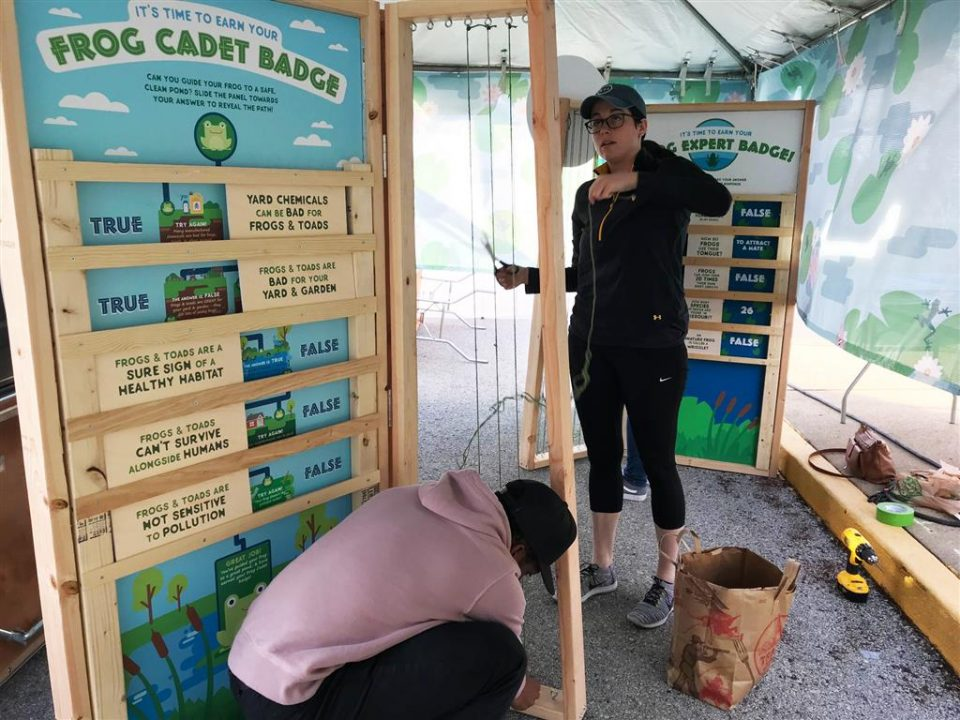 Graphic Designers Jess Burgess and Jayvn Solomon put the finishing touches on the Frog Cadet display.