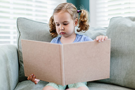 A stock photo of a little girl reading a big book