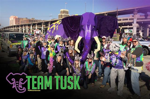 The PGAVia Team Tusk Elphie puppet on parade at St. Louis Mardi Gras with PGAV staffers